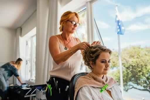 Bride having hair put up by Laurel stratford wedding hairstylist
