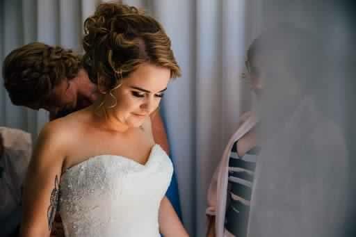 The bride getting her dress done up. Hair Laurel Stratford wedding hair